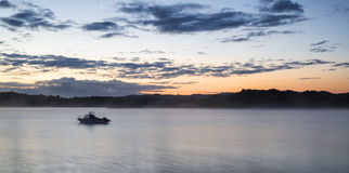Sunrise vibrant landscape of boat on calm lake. Sunrise landscape of boat on calm lake Stock Photos