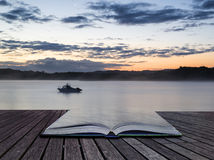 Sunrise vibrant landscape of boat on calm lake conceptual book i Royalty Free Stock Photography