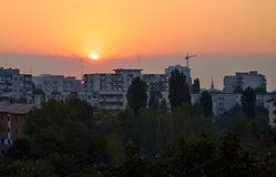 Sunrise view with the city. Buildings, trees and sun rays. Bucharest, Romania Royalty Free Stock Photography