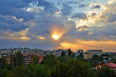 Sunrise view with the city. Buildings, trees and sun through the clouds. Bucharest, Romania Stock Photography
