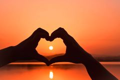 SUNRISE VIEW BETWEEN HEART SHAPE HANDS royalty free stock photography