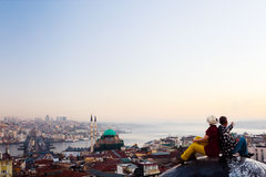 Sunrise View of large eastern City and Couple sitting on Roof Stock Photos