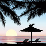 Sunrise view at resort. Seaside holiday background. Sunrise view at resort. Relaxing holiday landscape. Two chaise longue and parasol on beach with palm tree Royalty Free Stock Images