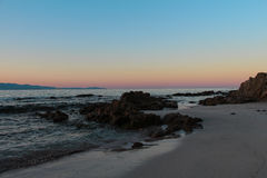 Sunrise with a view from a sandy shore. Beautiful sunrise with a view at sandy shore on Corsica, France royalty free stock image