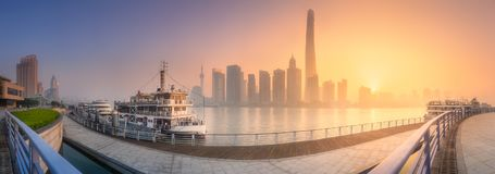 Sunrise view of Shanghai skyline with sunshine. Sunrise scenery view of Shanghai skyline and Huangpu river with ferry, China Royalty Free Stock Images