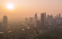 Sunrise view with skyscrapers on misty morning. JAKARTA, Indonesia - October 26, 2018: Beautiful aerial shot of sunrise view on misty morning with silhouette of stock photo