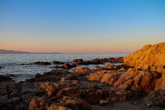 Sunrise with a view at a stony shore. Beautiful sunrise with a view at stony shore on Corsica, France stock images