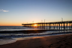 Sunrise Virginia Beach Fishing Pier. Sunrise silhouette of the Virginia Beach fishing pier with the beach in the foreground Stock Image