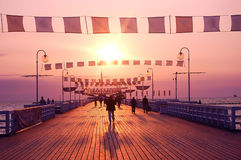 Sunrise walk. People walking on pier during sunrise royalty free stock images