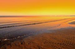 Sunrise with wave on beach Stock Photo