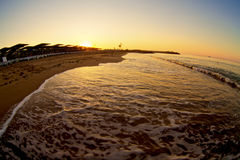 Sunrise with wave on beach. Small wave gently swapping on golden tropical beach Royalty Free Stock Photo