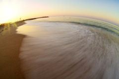 Sunrise with wave on beach. Small wave gently swapping on golden tropical beach Royalty Free Stock Image