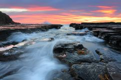 Sunrise waves flowing into rock chasm seascape. Beautiful sunrise lights up the clouds as waves flow into eroded rock chasm flowing over and around loose rocks Stock Photos