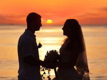 Sunrise wedding. Shape of a bride and groom on the beach at sunrise time Royalty Free Stock Photography