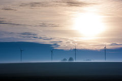 Sunrise with wind turbines. Foggy winter morning on the fields, with wind turbines in the background Stock Image