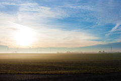 Sunrise with wind turbines. Foggy winter morning on the fields, with wind turbines in the background Stock Photo