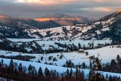 Sunrise in winter carpathians. Carpathian mountain rural area near peaks in snow on frosty sunrise in winter royalty free stock photography