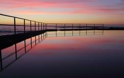 Sunrise at Wombarra Ocean Rock Pool. Sunrise views across the Wpmbarra ocean rock pool with reflections.  Wombarra NSW  Australia Stock Photography