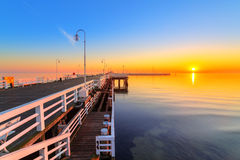 Sunrise at wooden pier on Baltic sea Stock Image