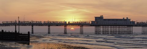 Sunrise at Worthing pier. Landscape view of Worthing Pier shortly after sunrise.  The sun has risen between the legs of the pier and has turned the sky an orange Stock Photos