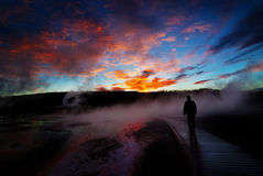 Sunrise Yellowstone Geysers with Man Silhouetted. Sunrise near Yellowstone geysers with steam and silhouette of person on boardwalk Royalty Free Stock Photos