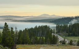 Sunrise in Yellowstone National Park. A dreamy drive through Yellowstone National Park in the morning with winding roads, misty clouds, and spectacular mountains royalty free stock images