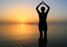 Sunrise yoga. Young woman in the yoga pose in Red Sea Stock Image