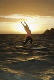 Sunrise yoga on paddle board. Woman doing yoga on her paddle board at sunrise Royalty Free Stock Photo