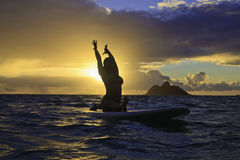 Sunrise yoga on paddle board Royalty Free Stock Photography