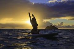 Sunrise yoga on paddle board. Woman doing yoga on her paddle board at sunrise in hawaii Royalty Free Stock Photography