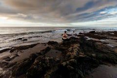 Sunrise yoga session on beach Stock Photos