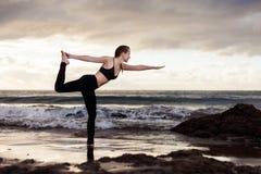 Sunrise yoga session on beach Stock Image