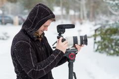 Wedding Videographer at Winter Wedding. SUNRIVER, OR - FEBRUARY 18, 2018: Male wedding videographer at a Winter wedding in Oregon filming in the cold with snow Stock Images