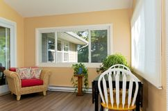 Sunroom with Furnishings and Window View. Interior of sunroom addition to home and decor including small table with chairs and view of home exterior from window stock photos