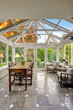 Sunroom patio area with transparent vaulted ceiling. Dining table set with sitting area stock image