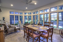 Sunroom remodel. Beautiful sunroom with table and chair and lots of windows stock image
