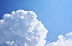 Suns rays hitting building cumulus top. A silver lined cloud darkens against a dark blue sky Royalty Free Stock Image