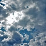 Suns rays hitting building cumulus top. A silver lined cloud darkens against a dark blue sky Stock Photo