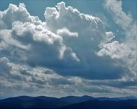 Suns rays hitting building cumulus top. A silver lined cloud darkens against a dark blue sky Royalty Free Stock Images