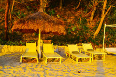 The suns rays at sunset light on the background of chairs facing the jungle Stock Photo