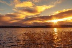 Suns Strahlen machen ihre Weise durch die Wolken über dem See bei Sonnenuntergang Schöner Glättungslandschaftshintergrund stockbilder