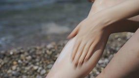 sunscreen Ένα κορίτσι λερώνει το πόδι με την κρέμα στην παραλία φιλμ μικρού μήκους