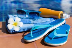 Sunscreen γυαλιών ηλίου μπλε παντόφλες και πετσέτα κρέμας στα σύνορα Στοκ Φωτογραφία
