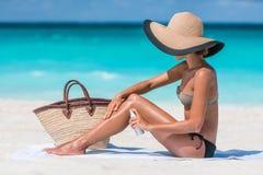 Sunscreen γυναίκα μπουκαλιών ψεκασμού που εφαρμόζει το λοσιόν σωμάτων Στοκ εικόνα με δικαίωμα ελεύθερης χρήσης