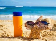 Sunscreen και αστερίας με τα γυαλιά ηλίου στην αμμώδη παραλία Στοκ εικόνες με δικαίωμα ελεύθερης χρήσης