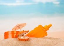 Sunscreen και κοχύλι με το μαργαριτάρι στη χρυσή άμμο Στοκ εικόνα με δικαίωμα ελεύθερης χρήσης