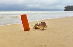 Sunscreen κρέμα, γυαλιά ηλίου στην παραλία στοκ εικόνα