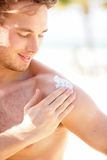 Sunscreen. Man putting sun screen / sun block on shoulder on sunny summer day during vacation on beach resort. Young handsome Caucasian male model smiling royalty free stock photos