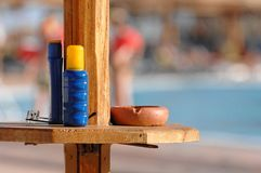 Sunscreen and ashtray at pool Stock Images