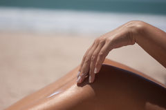 Sunscreen at the beach on the leg Royalty Free Stock Photo